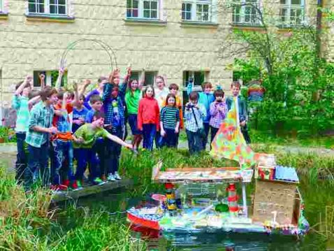 Kinder um einen Teich mit einem aus Müll gebauten Boot