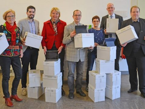 Mitarbeiter der Stadtverwaltung Trier posieren für das Foto mit Karton Boxen