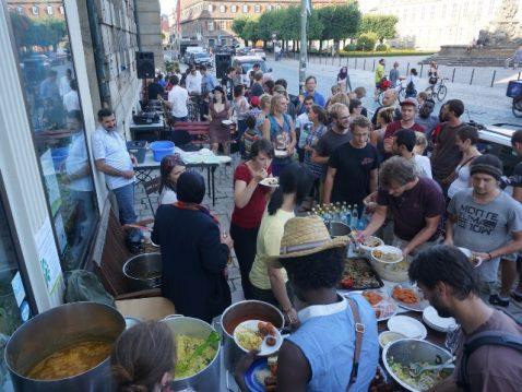 Menschen und Töpfe mit Essen vor Gebäude