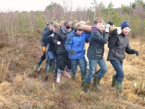 Kinder tragen einen Baumstamm auf einem Moor