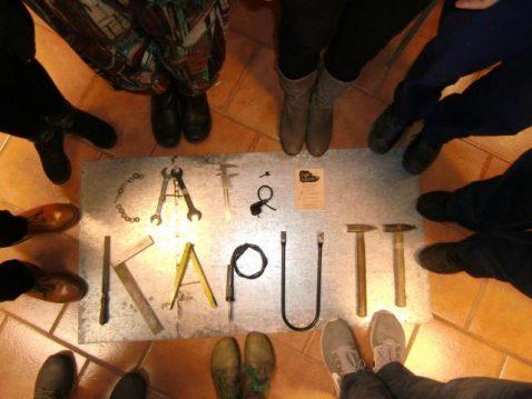 Die Wörter Café Kaputt, geschrieben mit Werkzeug, Füsse die drum herum stehen, Bild von oben gemacht