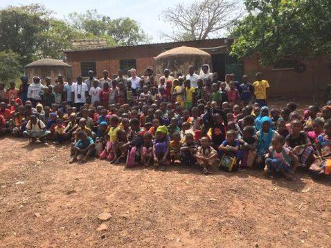 Kinder und Erwachsene im Senegal posieren für das Foto