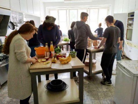 Junge Menschen in grosser Küche bereiten Essen vor