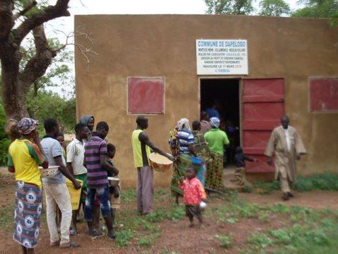 Burkiner in Burkina Faso stehen mit Schüsseln vor einem braunen Haus an