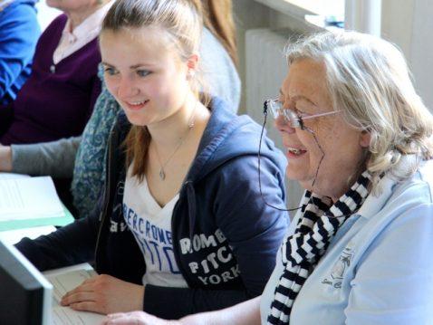 Junge Frau und ältere Frau arbeiten zusammen an einem Computer