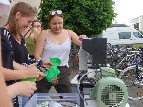 Schülerinnen arbeiten mit Abfall an einer Maschine