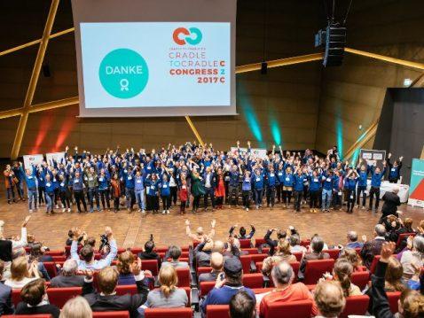 Kongress, viele Menschen auf der Bühne, aus dem Publikum fotografiert.
